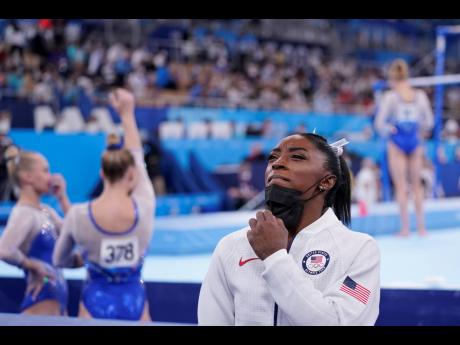 Simone Biles, of the United States, stands holding her mask after she exited the team final with apparent injury, at the 2020 Summer Olympics in Tokyo, Japan on Tuesday.