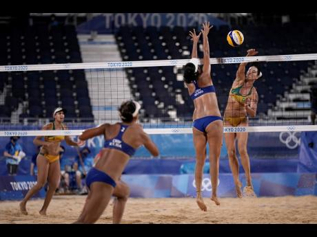 Agatha Bednarczuk (right) of Brazil, takes a shot as Wang Fan, (second right) of China, defends during a women's beach volleyball match at the 2020 Summer Olympics in Tokyo, Japan on Tuesday. Teammates Eduarda Santos Lisboa (left) of Brazil, and Xia Ziny