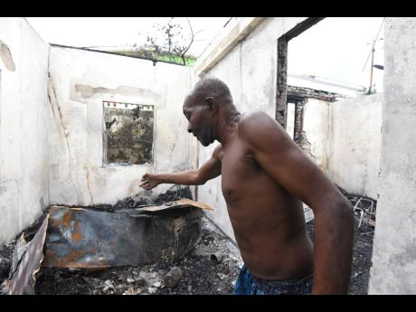 Oscar Palmer walks through one of the scorched rooms in his Kingston Gardens home on Tuesday. Arsonists attacked the family before dawn.