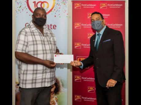 Lawrence Madden (left) of Church Services Development Fund receives a cheque from Nigel Holness, managing director, CIBC FirstCaribbean, in support of their programme targeting 100 students to receive vouchers, bursaries to high schools and universities, a