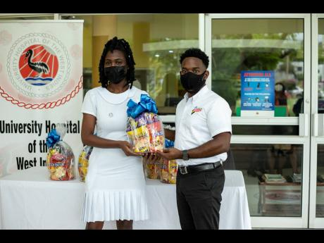 Nurse Princess Edwards of the University Hospital of the West Indies accepts her Nurses' Week gift basket from brand manager at the National Baking Company, Chris-Anthony Salter. In recognition of Nurses' Week 2021, the National Baking Company Limited