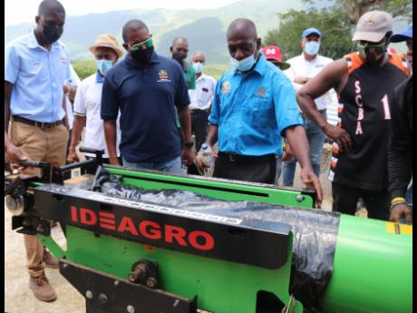Peter Myers (second right), technical assistant, Jamaica Dairy Development Board, demonstrates to Agriculture and Fisheries Minister Floyd Green (second left) the bagging of silage using the silage-packing machine at the handover-of- silage ceremony held a