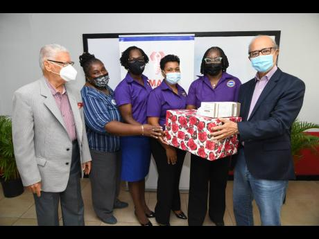 President of the Nurses Association of Jamaica (NAJ) Patsy Edwards Henry (second right), receives 300 high-quality masks from Michael Fraser (first right), chairman of the Jamaica Medical Foundation. At first left is Oliver Jones, chairman emeritus of the