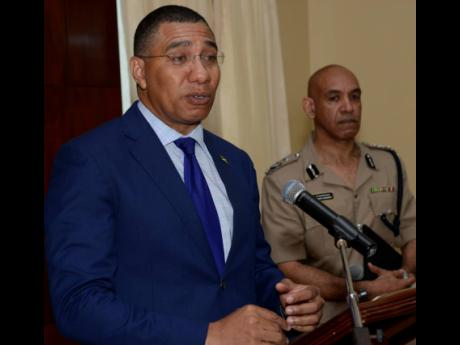 Prime Minister Andrew Holness announcing the imposition of a state of emergency for St James, Hanover, and Westmoreland during a press conference at Jamaica House on April 30, 2019. Looking on is Antony Anderson, the commissioner of police.