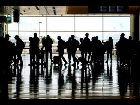 In this March 17, 2021 photo, travellers walk through the Salt Lake City International Airport.