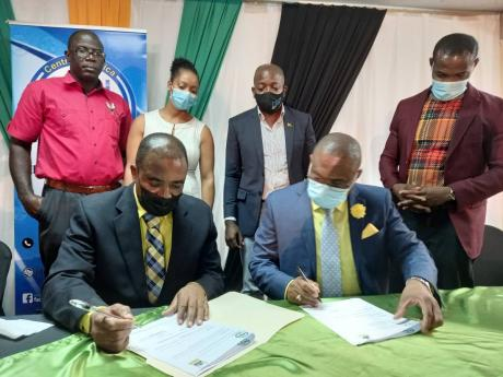 Chief Executive Officer of the Rural Agricultural Development Authority (RADA) Peter Thompson (seated, left)signs the contract for youth entrepreneurship training programme with Managing Director, Central Jamaica Social Development Initiative (CJSDI), Dami
