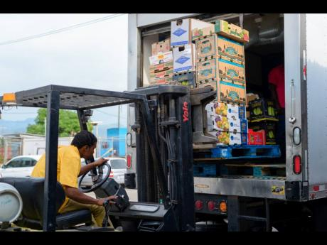 A forklift operator loads goods on a truck at Everything Fresh Limited in Kingston.