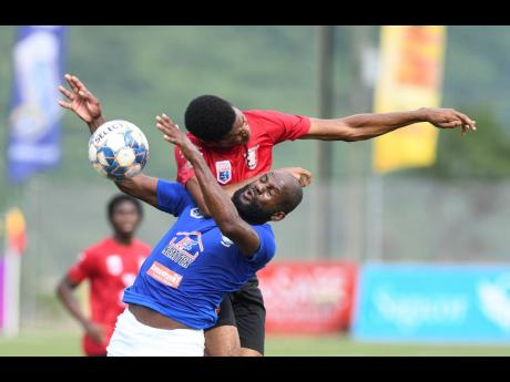 Mount Pleasant Football Academy's Francois Swaby (blue top) and Earl Simpson of Arnett Gardens get involved in an aerial battle during their Jamaica Premier League football match at the UWI/Captain Horace Burrell Centre of Excellence on Sunday, July 25,