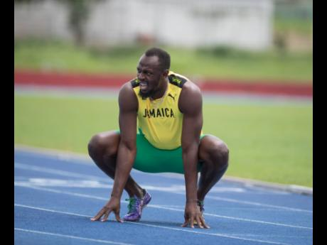 Olympic sprint great Usain Bolt catches his breath after competing in a Carmax promotional 800m race on July 13 at the University of the West Indies track named in his honour. The retired sprinter sputtered to a time of 2:39.