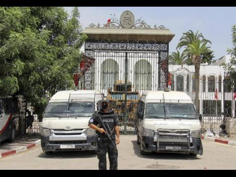 Police cars and a military armored personnel carrier block the entrance of the Tunisian parliament in Tunis on Tuesday. The Ennahda party, has called for dialogue, following President Kais Saeid's sacking of the prime minister and suspension of parliamen