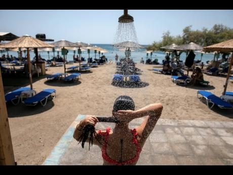 A woman takes a shower at a beach of Lagonissi village, a few miles southwest of Athens, on Thursday.