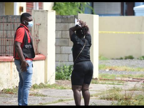 A policeman looks on at the distraught niece of a 55-year-old woman who died in an arson attack on West Avenue in Kingston Gardens on Thursday. The fire started about 3 a.m. and quickly engulfed the house. Firefighters from York Park and Half-Way Tree put