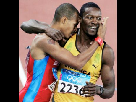 The Dominican Republic's Felix Sanchez and Jamaica's Danny McFarlane celebrate at the end of the Men's 400m hurdles final at the Olympic Games in Athens, Greece on Thursday, August 26, 2004. McFarlane finished runner-up behind Sanchez to claim a silv