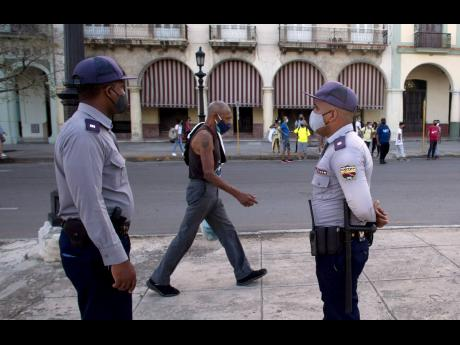 Police stand guard near the National Capitol building in Havana, Cuba, a day after protests against food shortages and high prices amid the coronavirus crisis.