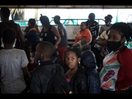 Migrants stand in line before boarding a boat that will take them to Capurgana, on the border with Panama, from Necocli, Colombia, Thursday, July 29. Migrants have been gathering in Necocli as they move north towards Panama on their way to the US border.