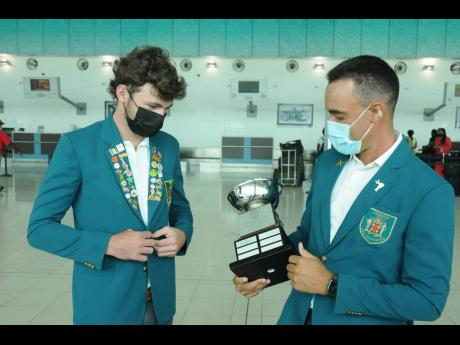 Jamaica's junior golf coach, Jonathan Newnham (right), looks at the James Moss Solomon Trophy with Rocco Lopez, before the team departed for the Caribbean Amateur Junior Golf Championships, to be held in the Dominican Republic.