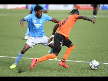 Tivoli's Devroy Grey (right) moving past Waterhouse's Denardo Thomas during Monday's Jamaica Premier League match at the UWI/Captain Horace Burrell Centre of Excellence. The game ended in a 1-1 draw.