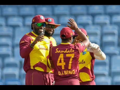 West Indies players celebrate the fall of a wicket during a recent T20 match against Australia.