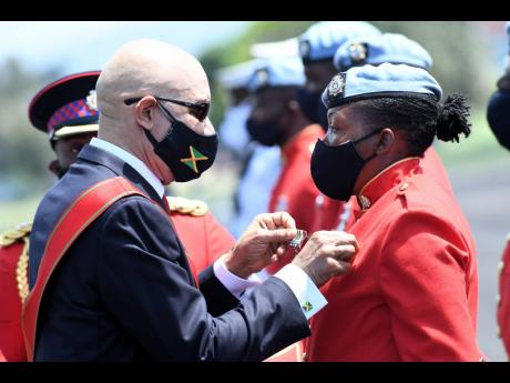 Governor General Sir Patrick Allen pins a medal on a solider yesterday during a ceremony to mark Armed Forces Day 2021 at the Jamaica Defence Force headquarters Polo Field, Up Park Camp on yesterday.