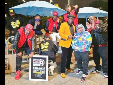 The Wu-Fam in celebration mode with their Billboard plaques.