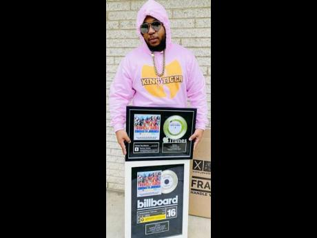 King Tiger shows off his Billboard plaques.