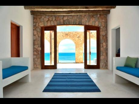 An amazingly simple interior, leads outdoors through archways to a swimming pool, above the sea.