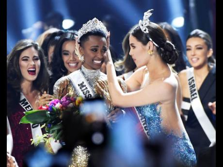 Tunzi (left), of South Africa, is crowned on-stage by Miss Universe 2018 Catriona Gray at the 2019 Miss Universe Pageant in Atlanta, Georgia. She described the moment as an out-of-body experience.