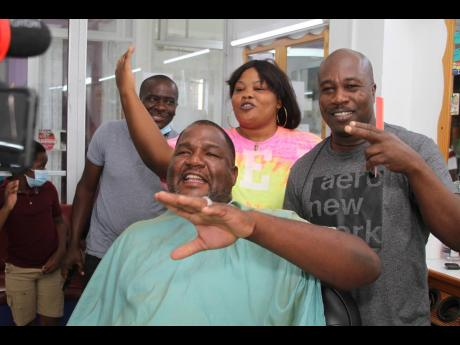Nathaniel Stewart/Photographer  Keith Thompson (right), father of Elaine Thompson Herah, celebrates her amazing 100m win at the Tokyo Olympics yesterday at his barber shop in Mandeville, Manchester with friends Frankie Davis (seated), Meleta Allen and Denn