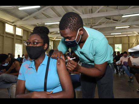 Ian Allen/Photographer  Dr Kapel Dowe administers the AstraZeneca COVID-19 vaccine to 18-year-old Kimberley Hamilton during yesterday's vaccination blitz at the Mona Ageing and Wellness Centre in St Andrew.