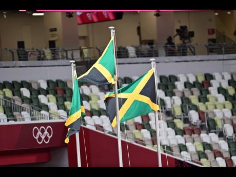 The Jamaican flags are hoisted during the medal ceremony for the women's 100 metres event.
