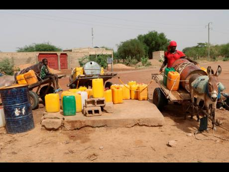 Residents fill up water containers in Dori, Burkina Faso. Violence by fighters linked to al-Qaida and the Islamic State in Burkina Faso is on the rise, and with it, so is the recruitment of child soldiers, according to reports.