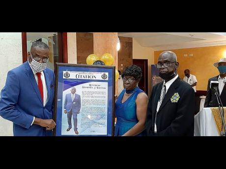 From left: Reverend Courtney Walters, retired Chaplain of the Jamaica Constabulary Force for Area One receives a citation from Paulella Morris, and retired Superintendent of Police John Morris who now serves as first vice president of the Retired Police Of