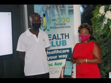 Dr Sherridene Lee (right), managing director of i-doc Concierge Wellness Services, presents a i-doc health club membership card to taxi driver Kenric Spence, who suffers from hypertension, during the launch at the Icon Mall in Fairview, Montego Bay, last T