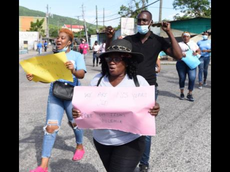Ian Allen Residents mark for peace in August Town St Andrew yesterday.