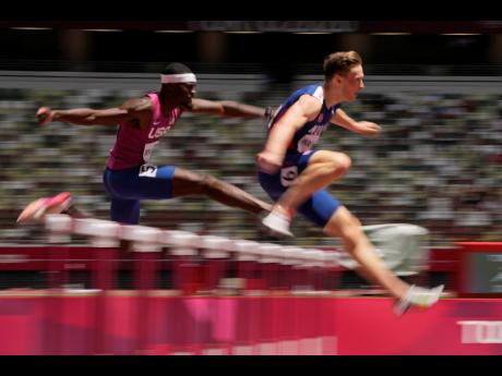 Karsten Warholm (right) of Norway, leads Rai Benjamin, of United States, on his way to a world record 45.94 seconds in the final of the Men's 400m hurdles at the 2020 Summer Olympics, in Tokyo, Japan on Tuesday.