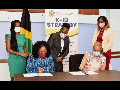Minister of Education, Youth and Information Fayval Williams (seated right) and Country Representative for Microsoft, Yamile Bustamante (seated left), sign a Memorandum of Understanding (MoU) for a five-year Digital Skills Programme, at the Ministry's Na
