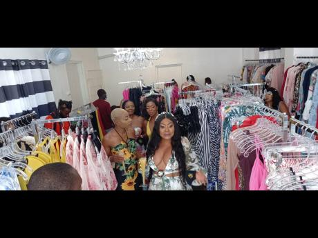 Store owner and designer Theresa White (foreground) shares a moment with well-wishers during the official opening of ChicByT fashion store in Port Antonio, Portland.