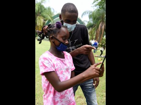 Sixteen-year-old St Thomas youth Jaheim Brown shows Addia Lobban how to manoeuvre a tablet that she received from the Ministry of Education, Youth and Information during a visit to Hope Gardens on Saturday. The teenager was commended for hosting a yearly s
