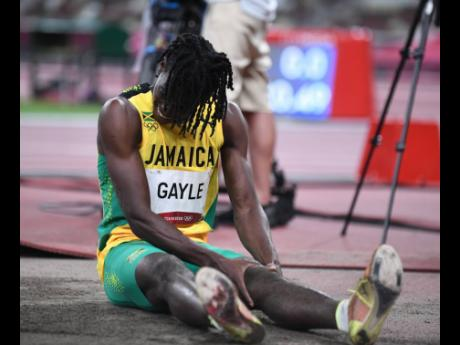 Jamaica's Tajay Gayle holds his injured knee while competing in the men's long Jump at the 2020 Tokyo Olympics in Japan on Saturday. He came 11th in the final.