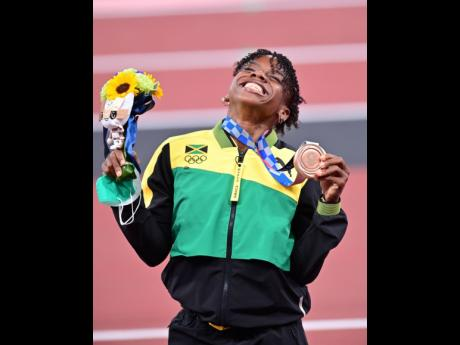 History-making Jamaican Megan Tapper celebrates becoming the first Jamaican female to win a bronze medal in the women's 100 metres hurdles, during the medal ceremony at the Tokyo 2020 Olympics at the Tokyo National Stadium in Tokyo, Japan, yesterday.