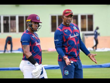 West Indies' coach Phil Simmons gives a few pointers to batsman Shimron Hetmyer during a practice session in Guyana, yesterday.