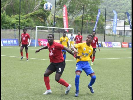 Marlon Martin from Arnett Gardens looks to control the ball ahead of Molynes United's Akeem Brown during the Jamaica Premier League football match at the University of the West Indies (UWI)/Jamaica Football federation (JFF) Captain Horace Burrell Centre