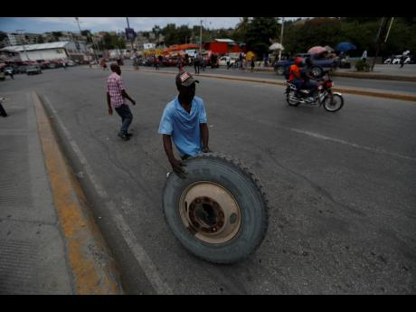 A worker rolls a tyre across the street in Port-au-Prince, Haiti, Monday, July 12, 2021.