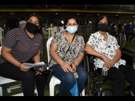 Three generations of Kirpalani family members turn up at the National Arena to be vaccinated against COVID-19 during the Vaccination Blitz on Saturday. They are (from left) Siya Kirpalani, 18 years old; her mother, Divya Kirpalani; and her grandmother, Jyo