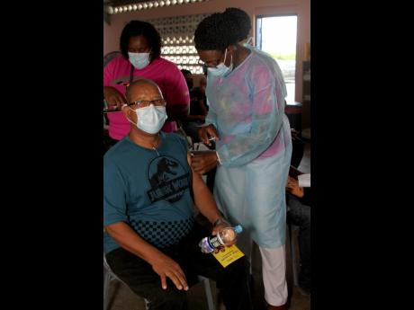 Nurse Nadine Rowe administers the first dose of the AstraZeneca vaccine to Thaddeus Blight, who was encouraged by his wife, Veronica, to get vaccinated. Scores of persons turned out on Saturday at Denbigh Primary School to receive their first or second dos
