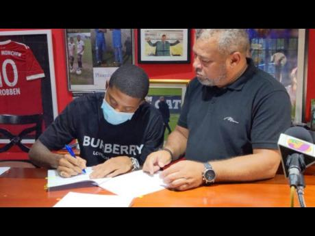 Reggae Boy Leon Bailey (left) made his move to the English Premier League official when he signed a contract with Aston Villa Football Club yesterday. The signing took place at the Phoenix All Stars Academy headquarters in Kingston. Looking on is his adopt