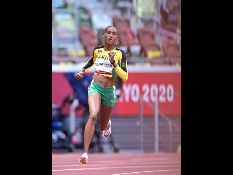 Stephenie-Ann McPherson cruising to an easy victiory in the women's 400m heats yesterday.