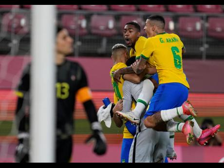 Brazil's players celebrate after defeating Mexico in a penalty shoot-out during the men's soccer semi-final match yesterday.