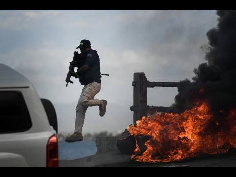 A police officer abandons his vehicle during a demonstration that turned violent in which protesters demanded justice for the assassinated President Jovenel Moise in Cap-Haitien, Haiti, on July 22.