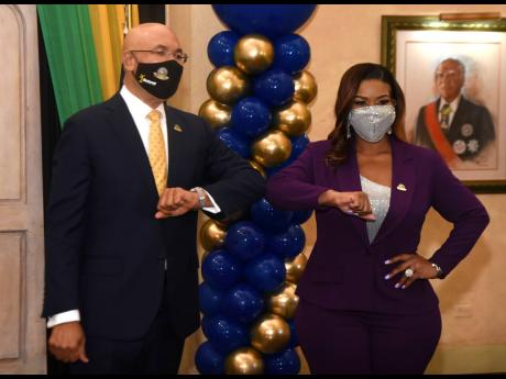Dressed in a purple power suit and sequinned mask, Khadine 'Miss Kitty' Hylton (right), bumps elbows with Sir Patrick Allen, governor general of Jamaica.